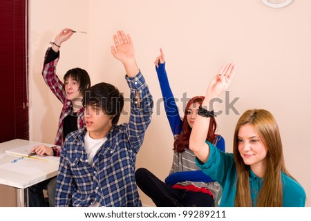 Students with hands raised, a motivated group - stock photo