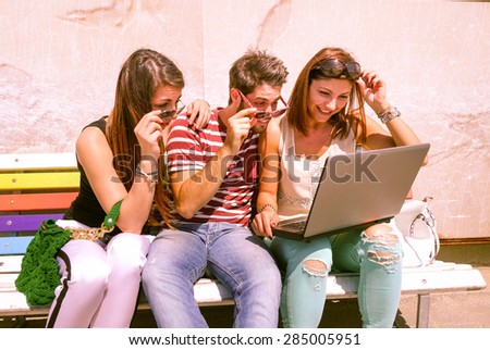 Students with laptop looking surprised by results of examinations - Three cheerful young best friends sharing news and web surfing - Modern concept of youth and communication - Marsala filter look - stock photo