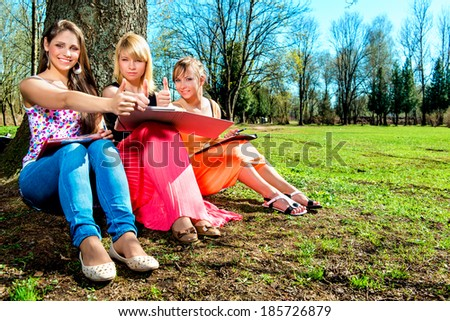 Students with thumbs up outdoors - stock photo