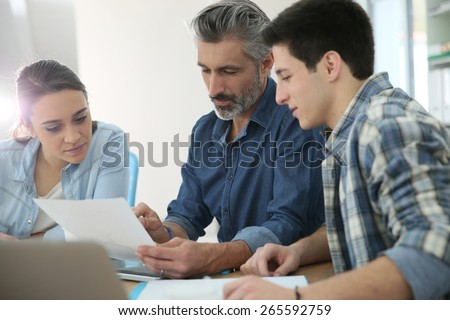Students with trainer working on project - stock photo