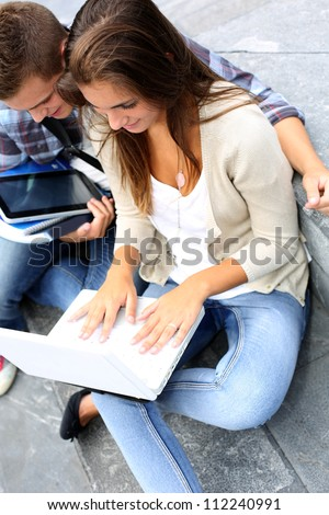 Students working on laptop computer outside class - stock photo