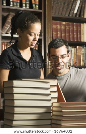Students Working with stacks of books in front of them, and books in the background. Vertically framed photo. - stock photo