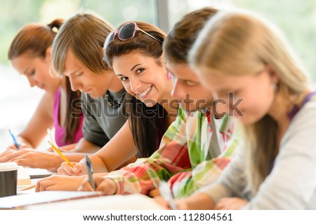 Students writing at high-school exam teens study campus academic class - stock photo