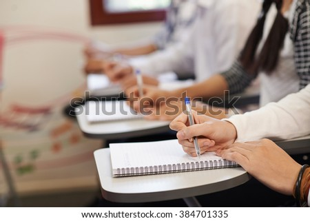 Students writing in textbooks, selective focus - stock photo