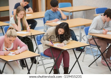 Students writing in the exam hall of the college - stock photo