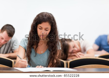 Students writing while their classmate is sleeping in an amphitheater - stock photo