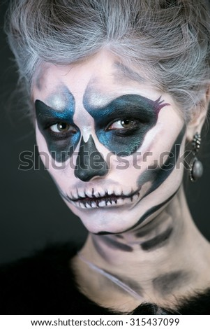 Studio art photo of the girl in the image of a skeleton on a black background
