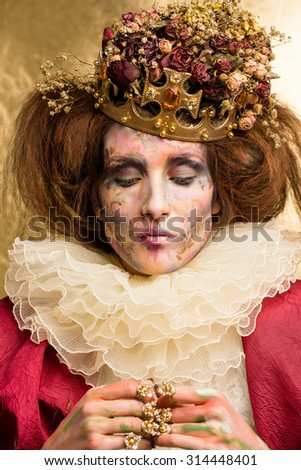 Studio art photo of the girl in the image of the Queen on a gold background. the art of makeup.