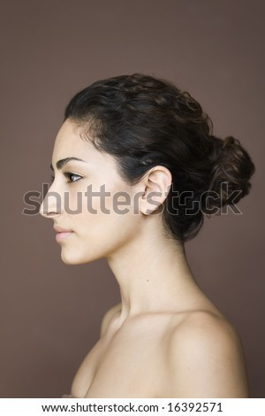 Studio beauty portrait of bare-shouldered Italian-American woman in profile