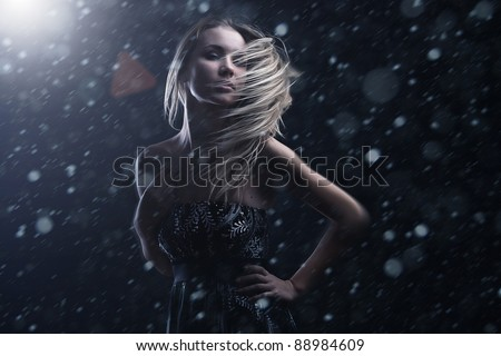 studio black and white portrait of attractive young woman on dark background - stock photo