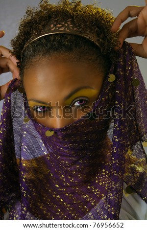 Studio close-up of a lovely mature black woman holding a scarf or veil over her face, revealing her powerful and mysterious eyes. - stock photo