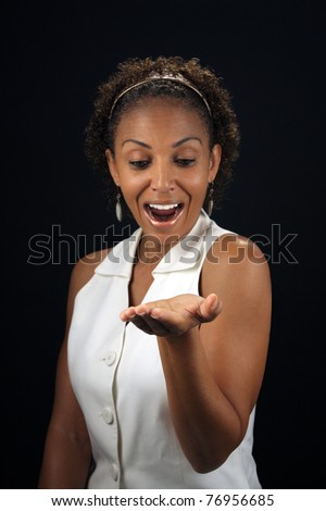 Studio close-up of an excited, lovely, mature black woman with her palm up and extended, parallel to the floor, allowing for easy insertion of products or graphics for her to be holding. - stock photo