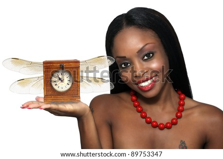 Studio close-up of an extraordinarily beautiful young woman with a bright, warm smile and an antique clock with wings in her extended hand.