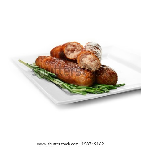 Studio close up of grilled pork sausages stacked against a white surface on a bed of rosemary sprigs with soft shadows. Copy space. - stock photo