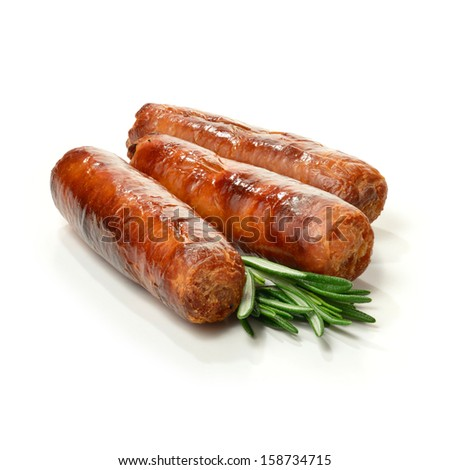 Studio close up of pin sharp focus grilled pork sausages stacked against a white surface with rosemary sprigs and soft shadows. Copy space. - stock photo