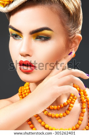 Studio close up portrait of young fashion model with healthy skin and rowan accessories on neck