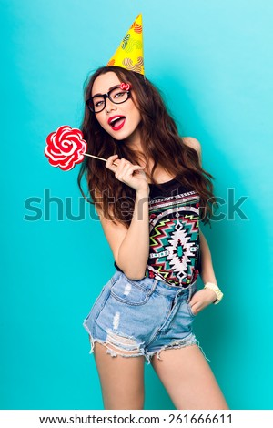 Studio closeup colorful portrait of young sexy funny fashion crazy  girl posing on  blue wall background in summer style outfit with pink lollipop wearing paper  hat  and cute glasses.  - stock photo
