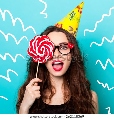 Studio closeup colorful portrait of young sexy funny fashion crazy woman posing on blue wall background in summer style outfit with pink lollipop wearing paper hat and cute glasses. - stock photo