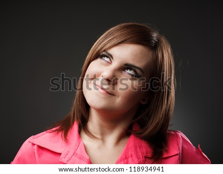 Studio closeup portrait of a young woman looking up - stock photo