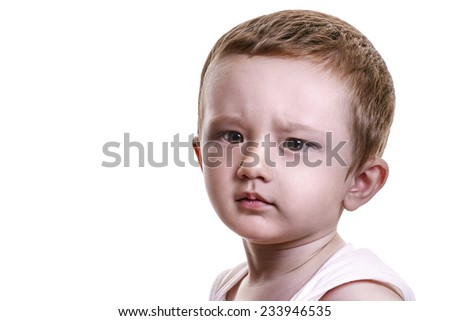 Studio closeup portrait of little baby boy with serious face looking displeased, isolated on white background - stock photo