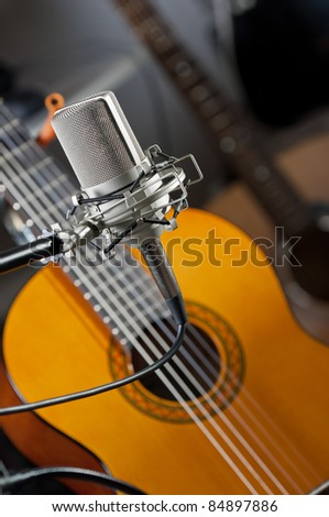 Studio condenser mic in the foreground with an acoustic guitar blurred out in the background - stock photo
