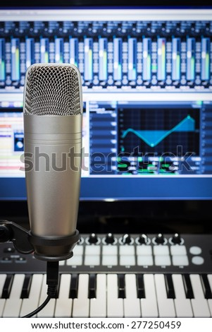 studio condenser microphone, midi keyboard synthesizer & digital mixer on screen monitor for computer music or broadcasting concept background - stock photo