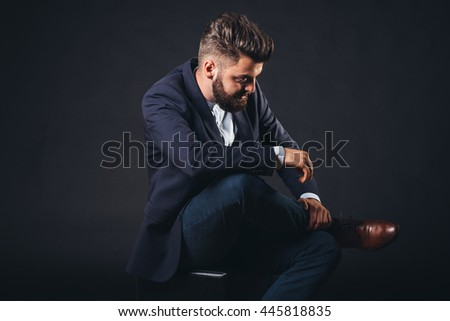 studio corporate portrait, bearded man sitting in isolated black, homogeneous