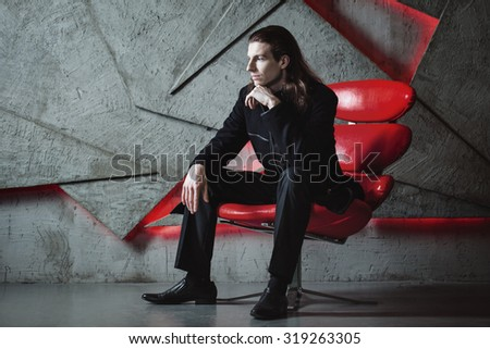 Studio fashion of young handsome man in coat. - stock photo