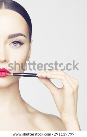 Studio fashion photo of beautiful young lady applied lipstick.  Perfect face makeup - stock photo