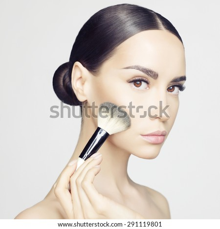 Studio fashion photo of beautiful young lady applying blush. Beauty and care. Extension eyelashes. Spa salon. Perfect face makeup - stock photo