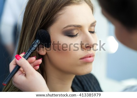 Studio fashion photo of beautiful young lady applying blush. Beauty and care. Extension eyelashes. Spa salon. Perfect face makeup