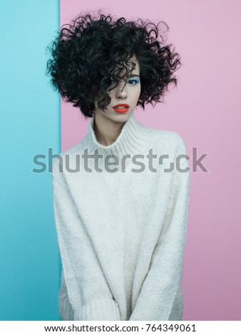 Studio fashion portrait of beautiful asian woman in oversize pullover on colorful pastel background. Stylish look book. Autumn Winter season. Bright spring