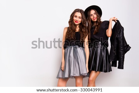 Studio fashion portrait of two elegant young women in fall stylish outfit posing in studio. Fashionable girls in skirts, bright make up, monochrome  clothes.  - stock photo