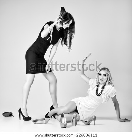 Studio fashion shot: the battle of two beautiful women (blonde and brunette). Black and white - stock photo