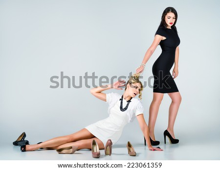 Studio fashion shot: the confrontation of two cute women (blonde and brunette) - stock photo