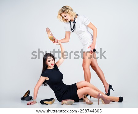 Studio fashion shot: the confrontation of two lovely women (blonde and brunette) - stock photo
