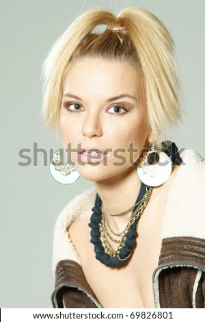 studio fashion style portrait of young attractive woman in leather jacket
