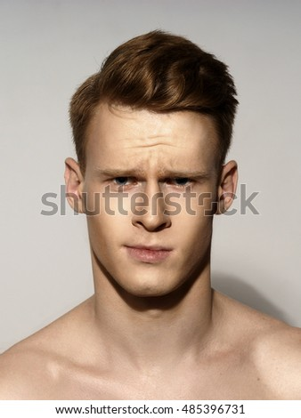 Studio fashion style portrait of young calm handsome red hair man. Closeup face portrait on gray background