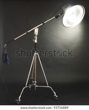 Studio flash with beauty dish on black background - stock photo