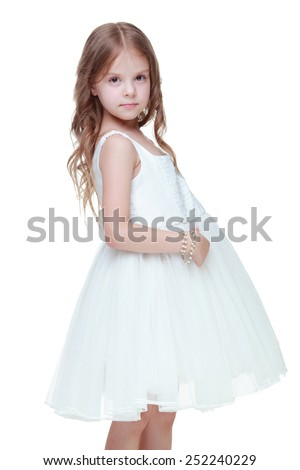 Studio image of a beautiful emotional girl with beautiful hair in a white dress on Beauty and Fashion - stock photo