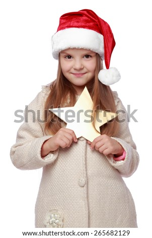 Studio image of a beautiful happy little girl with long blond hair in Santa hat holding christmas golden star isolated on white/Christmas portrait of a cute child in a Santa's hat - stock photo