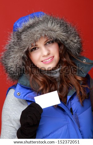 Studio image of a charming cheerful girl in warm winter clothes holding a blank white business card on a red background on Holiday - stock photo