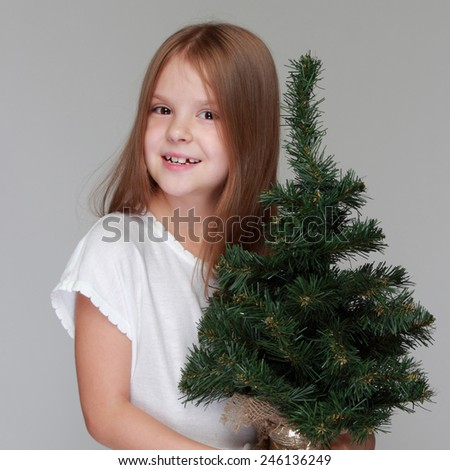 Studio image of a charming young girl in a white dress holding a small Christmas tree on a gray background on Holiday - stock photo