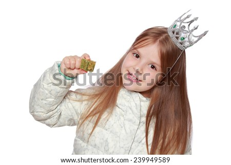 Studio image of a cute cheerful little girl in a warm white coat with a crown on his head holding a small gift isolated on white on Holiday - stock photo
