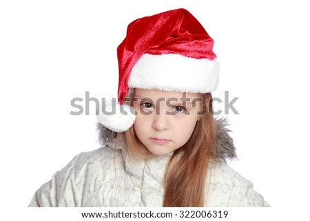 Studio image of a sad girl in a winter down jackets in Santa's hat isolated on white
