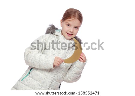 Studio image of a smiling pretty little girl with a sweet smile in a warm winter coat holding a golden moon isolated on white on Christmas