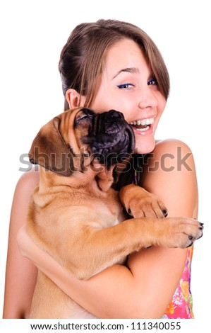 studio image of a young woman, with her bullmastiff dog, hugging it, both posing, looking happy and smiling - stock photo