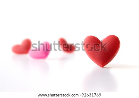Studio image of four Valentine hearts with focus on the foreground. Isolated on white. Copy space.