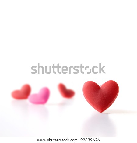 Studio image of four Valentine hearts with focus on the foreground. Isolated on white. Copy space. 21x21 cm square crop. - stock photo