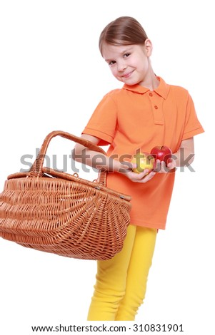 Studio image of lovely little girl holding yummy apples and picnic basket isolated over white background - stock photo